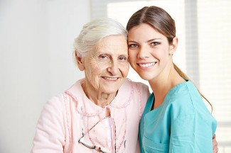 smiling aide embracing elderly woman